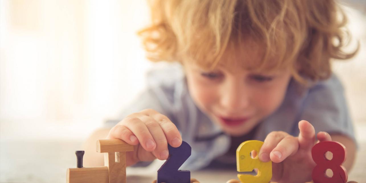 Un enfant jouant avec un petit train en bois